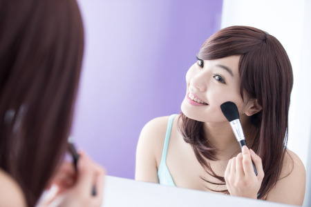 asia women: Close up of Smile woman with makeup brushes near face and look mirror. asian beauty Stock Photo