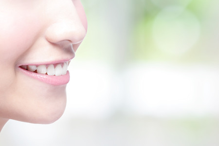 Beautiful young woman health teeth close up and charming smile. with green background, asian beauty 스톡 콘텐츠