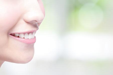 Krásná mladá žena zdravotní zuby zblízka a okouzlující úsměv. se zeleným pozadím, asijských krása