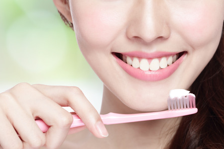 maleza: Primer plano de la sonrisa cepillarse los dientes mujer. grande para el concepto de cuidado dental de la salud, con la naturaleza de fondo verde. belleza asiática Foto de archivo