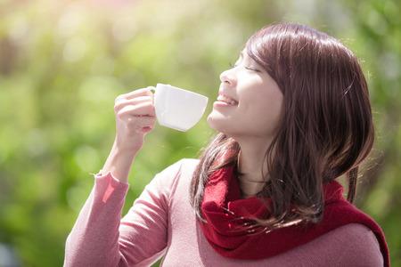 улыбаться молодая женщина, держащая чашку кофе или чая и носить зимнюю одежду с зеленым фоном, азиатской красоты