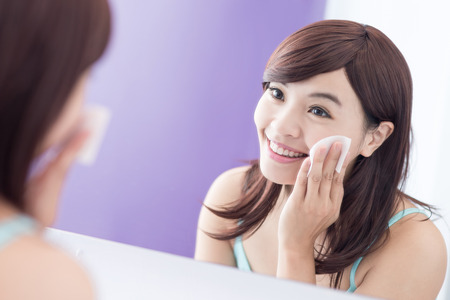 mirror face: Close up of Smile woman remove makeup by Cleansing Cotton and look mirror. asian beauty Stock Photo