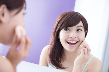 mujer maquillandose: Hermosa Mujer que usa la esponja cosm�tica en cara con sonrisa y la mirada del espejo. belleza asi�tica