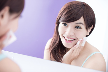 asian home: Close up of Smile woman remove makeup by Cleansing Cotton and look mirror. asian beauty Stock Photo