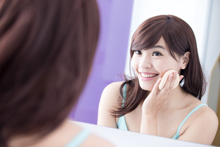 young woman face: Beautiful Woman using cosmetic sponge on face with smile and look mirror. asian beauty Stock Photo