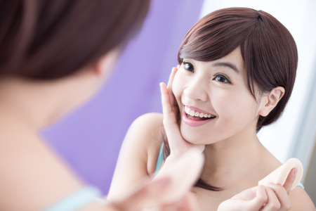 girl care: Beautiful Woman using cosmetic sponge on face with smile and look mirror. asian beauty Stock Photo