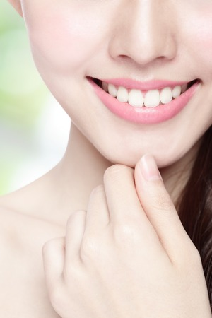 smile close up: Beautiful young woman health teeth close up and charming smile. Isolated on green background, asian beauty
