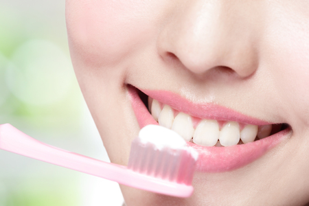 woman face close up: Close up of Smile woman brush teeth. great for health dental care concept, with nature green background. asian beauty