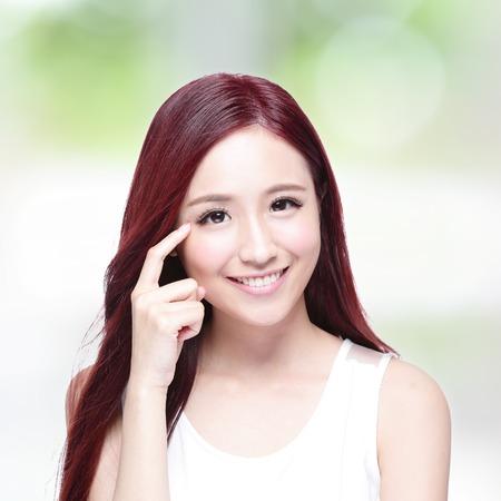 ojos verdes: Mujer de la belleza con una sonrisa encantadora a usted con la piel de la salud, los dientes y el pelo con la naturaleza de fondo verde, belleza asi�tica