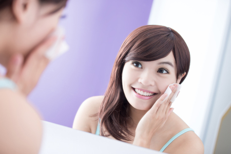 mujer maquillandose: Cerca de la mujer Sonrisa quitar el maquillaje por la limpieza del algodón y mirar el espejo. belleza asiática Foto de archivo