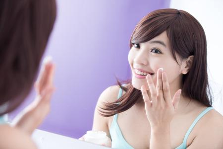 espejo: Retrato de una mujer joven de aplicar la crema hidratante en la cara y la mirada bonita espejo. belleza asi�tica