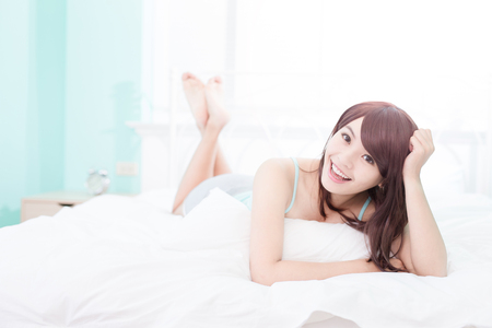 relaxing at home: Health woman Smile to you and she lying on the bed in the morning , asian girl