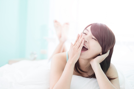 asia women: Charming woman yawn and she lying on the bed in the morning , asian girl Stock Photo