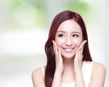 Schönheitsfrau mit einem charmanten Lächeln, Sie mit der Gesundheit der Haut, Zähne und Haare mit der Natur grünen Hintergrund, asiatische Schönheit