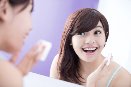 Close up of Smile woman remove makeup by Cleansing Cotton and look mirror. asian beauty