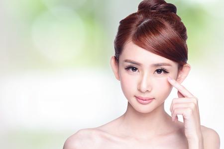 ojos verdes: Joven y bella sonrisa que señala su ojo, el concepto de cuidado de la vista de la salud, modelo de belleza asiática Foto de archivo