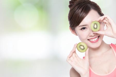 kiwi fruta: Mujer de la belleza y la fruta de kiwi - La mujer es la dieta saludable con la naturaleza de fondo verde, hembra asiática