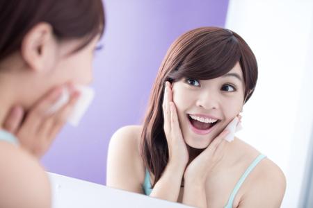 Nahaufnahme von Lächeln Frau entfernen Make-up von Cleansing Cotton und freuen Spiegel. Asian Beauty