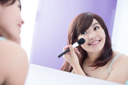 maquillaje de ojos: Cerca de la mujer de la sonrisa con pinceles de maquillaje cerca de la cara y la mirada del espejo. belleza asi�tica