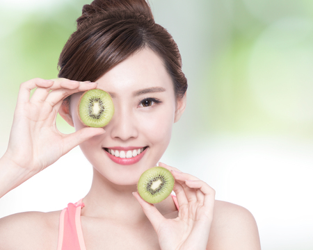 Beauty woman and Kiwi fruit - The woman is dieting healthy with nature green background, asian female Stock Photo