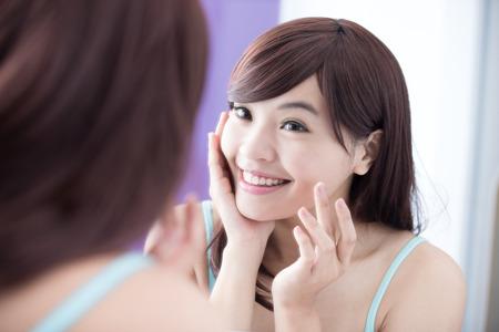 Porträt der jungen Frau, die Anwendung Feuchtigkeitscreme Creme auf ihr hübsches Gesicht und Blick Spiegel. Asian Beauty