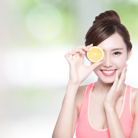 ojos verdes: Demostración de la mujer feliz en beneficio de naranja a la salud, belleza asiática