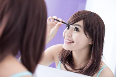 eyelashes: Close up of Smile woman applying mascara on her long eyelashes and look mirror. asian beauty Stock Photo