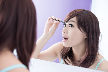 woman in bath: Close up of Smile woman applying mascara on her long eyelashes and look mirror. asian beauty Stock Photo