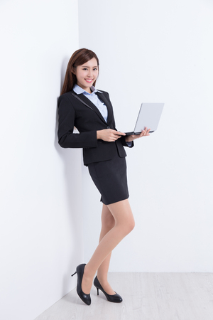 use computer: business woman lean wall and use computer with white wall background, great for your design or text, asian Stock Photo