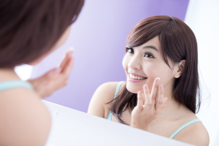 girl models: Portrait of young woman applying moisturizer cream on her pretty face and look mirror. asian beauty
