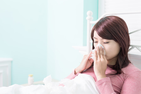 gripe: Mujer enferma estornudos en el tejido. La gripe y la mujer sorprendida en fr�o.