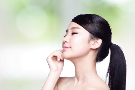 charming woman: Beautiful Skin care woman Face smile and enjoy carefree isolated on nature green background. asian Beauty Stock Photo