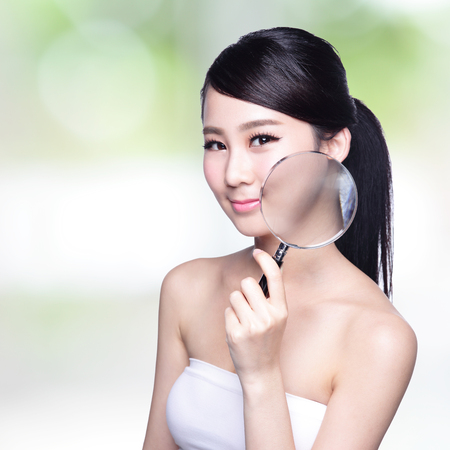 woman face close up: young woman with perfect skin and magnifying glass check it , concept for skin care, asian Stock Photo