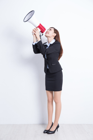 mujer cuerpo entero: business woman talking in megaphone with white wall background, great for your design or text, asian Foto de archivo