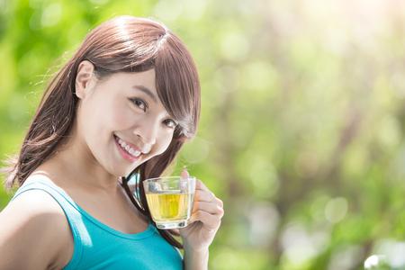 자연과 함께 뜨거운 차를 마시는 아름 다운 젊은 여자 녹색 배경, 건강 한 라이프 스타일 개념, 아시아 아름다움