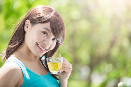 tea hot drink: Beautiful Young Woman drinking hot tea with nature green background, healthy lifestyle concept, asian beauty Stock Photo