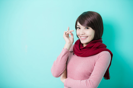 winter weather: Young beautiful woman wearing winter clothing and smile to you isolated on green background, asian beauty