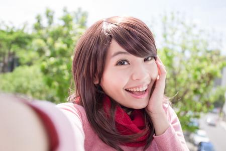 Young beautiful woman wearing winter clothing and photo selfie, asian beauty Foto de archivo