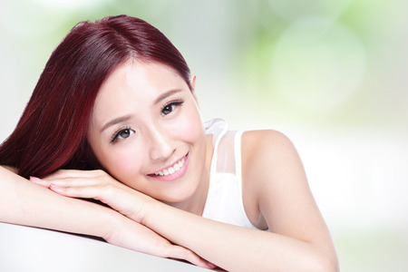 charming girl: Charming woman face Smile to you close up while lying with nature green background, asian girl