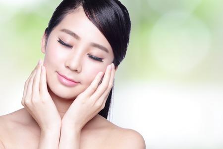 cosmeticos: Hermosa mujer de cuidado de la piel de la cara sonrisa y disfrutar sin preocupaciones aisladas sobre fondo de naturaleza verde. Belleza asi�tica