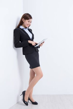 chinese lady: business woman lean wall and use digital tablet pc with white wall background, great for your design or text, asian