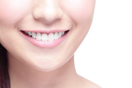 blanc: Belles jeunes dents de la santé de la femme se referment et charmant sourire. Isolé sur fond blanc, la beauté asiatique
