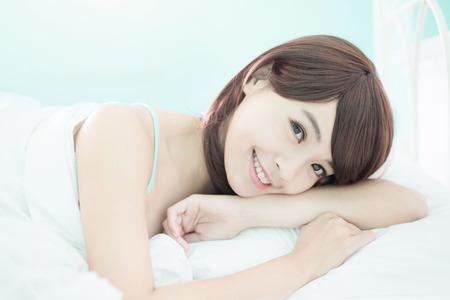 skönhet: Hälsa kvinna leende till dig och hon ligger på sängen på morgonen, asiatisk tjej