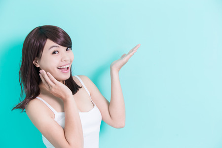 Happy young woman show something isolated on green background, asian beauty Stock Photo
