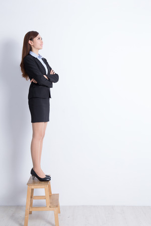 asian lady: business woman stand on a chair and look with white wall background, great for your design or text, asian Stock Photo