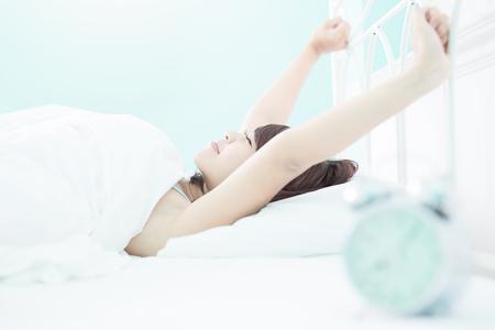 lächeln Frau aufwachen, die auf dem Bett in den Morgen, asiatische Mädchen Standard-Bild