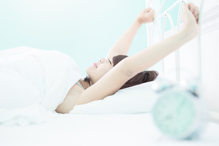 comfortable: smile woman wake up on the bed in the morning , asian girl