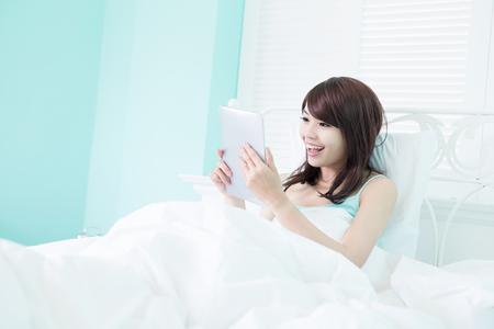 mujer en la cama: Mujer feliz utilizar la tableta digital en la cama por la mañana, asiatico Foto de archivo