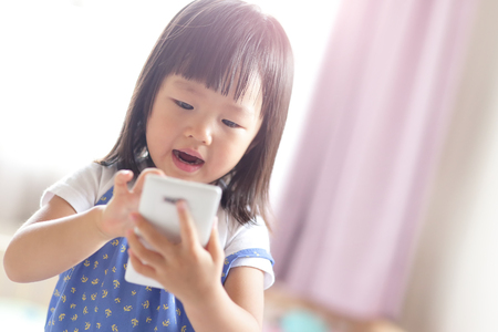 asia smile: child girl happy look smart phone. asian child Stock Photo
