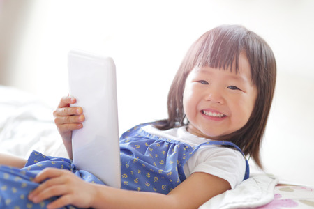 child girl happy play game with digital tablet PC. asian child Stock Photo